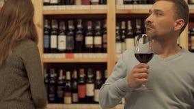 Condizione bella dell'uomo con il vetro di vino rosso in negozio di alcolici La donna nei precedenti sta scegliendo una bottiglia video d archivio