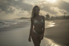 Condizione bionda adorabile nella bella posa sulla spiaggia di sabbia nera, tramonto rosa fotografie stock