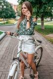 Condizione castana della donna della bella ragazza nel parco su una bicicletta Chiamate dal telefono di estate nella città sui pr fotografie stock libere da diritti