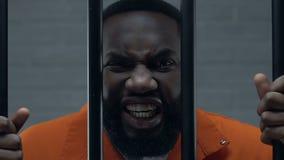 Condizione criminale afroamericana aggressiva nella prigione con le mani sulle barre della prigione video d archivio