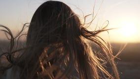 Condizione dai capelli lunghi della giovane donna dal telefono cellulare posteriore di usi a fondo vago città con il tramonto o l archivi video