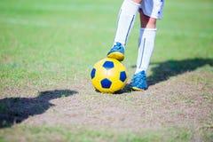 Condizione del giocatore di football americano del bambino e fare un passo sulla palla immagine stock libera da diritti