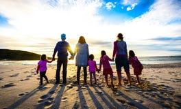 Condizione del gruppo degli amici e della famiglia sul tenersi per mano della spiaggia fotografia stock