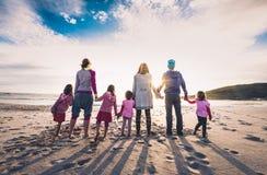 Condizione del gruppo degli amici e della famiglia sul tenersi per mano della spiaggia fotografie stock
