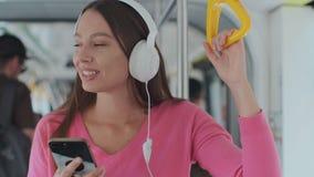 Condizione del passeggero della giovane donna con le cuffie e lo smartphone mentre muovendosi nel tram moderno, godente del viagg stock footage