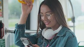 Condizione del passeggero della giovane donna con le cuffie e lo smartphone mentre muovendosi nel tram moderno, godente del viagg video d archivio