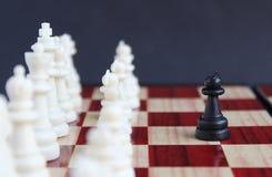 Condizione del pegno del nero del pezzo degli scacchi davanti ad un intero gruppo di pezzi degli scacchi bianchi fotografia stock