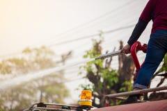 Condizione del personale sull'autocisterna con l'ugello di estinzione di incendio della tenuta e sul tubo flessibile con acqua de immagine stock