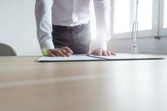 Condizione dell'uomo d'affari alla sua scrivania che pende per firmare un contrario fotografia stock libera da diritti