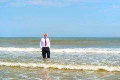 Condizione dell'uomo di affari alla spiaggia immagini stock libere da diritti