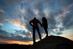 Condizione dell'uomo e della giovane donna sulla roccia e guardare per eseguire le nuvole Con il bello tramonto su fondo fotografia stock libera da diritti