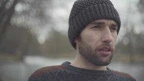 Condizione dell'uomo frustrata ritratto vicino al parco del fiume in primavera che distoglie lo sguardo vicino su L'uomo nervoso  video d archivio