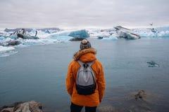 Condizione dell'uomo su un ghiaccio in un jokulsarlon Islanda della laguna del ghiacciaio durante il bello giorno soleggiato fotografia stock