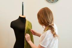 Condizione della cucitrice e raddrizzare panno verde sul manichino in studio di cucito fotografia stock