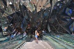 Condizione della donna sulle scale di uno spazio rispecchiato fotografia stock