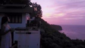 Condizione della giovane donna sul balcone, guardante il tramonto e bevente caffè caldo con il bello paesaggio della montagna sop stock footage
