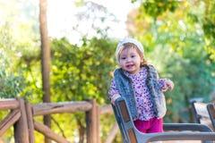 Condizione della ragazza del bambino in una sedia e sorridere all'aperto immagini stock