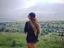 Condizione della ragazza ed ammirare la città da sopra Immagine Stock