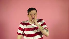 Condizione di tosse dell'uomo sul fondo rosa Ritenere indisposto o malato archivi video