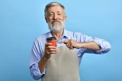 Condizione felice dell'uomo anziano con la tazza eliminabile ed esaminare la macchina fotografica immagine stock