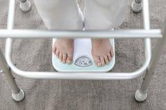 Condizione femminile di Eldely sulla bilancia, la sua misura 54 del peso Immagini Stock