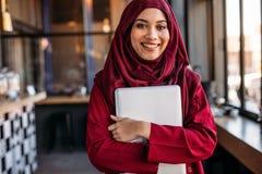 Condizione femminile musulmana con il computer portatile alla caffetteria fotografia stock libera da diritti