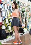 Condizione femminile nel negozio di articoli sportivi con le palle e la racchetta Fotografia Stock
