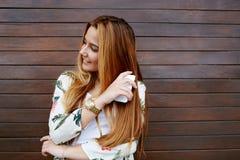 Condizione femminile sorridente splendida con il telefono cellulare contro il fondo di legno della parete Fotografia Stock Libera da Diritti