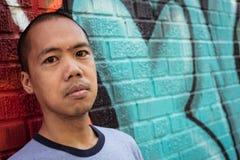 Condizione maschio asiatica contro la parete dei graffiti Immagine Stock Libera da Diritti