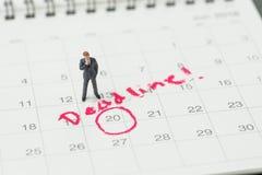 Condizione miniatura dell'uomo di affari sul calendario da tavolino con il cerchio rosso alla data importante con il termine, lo  immagini stock