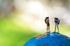 Condizione miniatura dello zaino della viandante e del viaggiatore sul globo per il turista e l'avventura intorno al mondo per il immagine stock