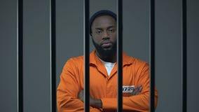 Condizione nera del prigioniero maschio con le mani attraversate sul petto e sullo sguardo alla macchina fotografica stock footage