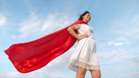 Condizione sexy sul campo in un mantello rosso, mantello della ragazza del supereroe che fluttua nel vento sogni della ragazza di video d archivio