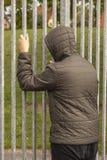 Condizione sola dell'adolescente fuori di un recinto del metallo con le sbarre di ferro e lo sguardo dentro Solitudine e concetto fotografia stock