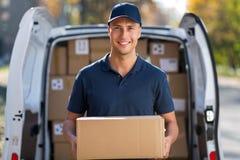 Condizione sorridente del fattorino davanti al suo van holding un pacchetto fotografia stock