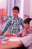 Condizione sorridente del ragazzo allo scrittorio vicino ai suoi compagni di classe fotografie stock libere da diritti