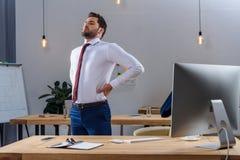 condizione stanca ed allungamento dell'uomo d'affari Immagini Stock