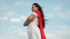 Condizione sul campo in un mantello rosso, mantello della ragazza del supereroe che fluttua nel vento Primo piano sogni della rag archivi video
