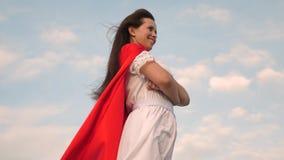 Condizione sul campo in un mantello rosso, mantello della ragazza del supereroe che fluttua nel vento Primo piano sogni della rag video d archivio