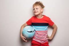 Condizione sveglia del ragazzino con il pallone da calcio ed esaminare macchina fotografica Isolato su bianco Ritratto dello stud immagine stock