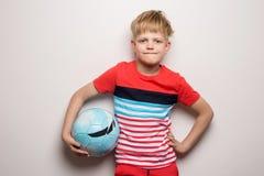 Condizione sveglia del ragazzino con il pallone da calcio ed esaminare macchina fotografica Isolato su bianco Ritratto dello stud fotografia stock libera da diritti