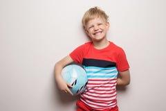 Condizione sveglia del ragazzino con il pallone da calcio ed esaminare macchina fotografica Isolato su bianco Ritratto dello stud fotografie stock