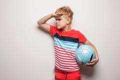 Condizione sveglia del ragazzino con il pallone da calcio ed esaminare macchina fotografica Isolato su bianco Ritratto dello stud fotografia stock
