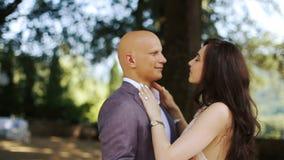 Condizione tenera sorridente della magra della donna e dell'uomo l'un l'altro sul cortile verde archivi video