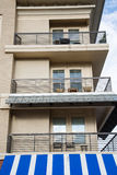 Condo Balconies Over Blue and White Awning Stock Image