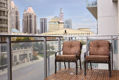 Condo balcony overlooking downtown mississauga. Condominium mezzanine with two brown chairs over looking downtown buildings. Street with seen trough glass Stock Photography