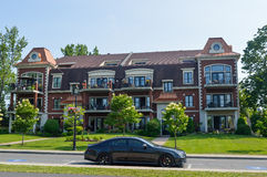 Condo building in Chambly downtown and a black car. Chambly, Canada - 24 juin, 2016: Condo building in Chambly downtown and a black car Royalty Free Stock Photo