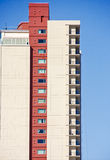 Condo Tower From Side with Red Column. A modern high rise condo tower from side with red column against blue sky Stock Image