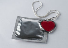 Condom with chain and heart Royalty Free Stock Photo