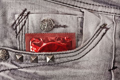 Condom in the grey jeans. A red condom in a pocket of jeans Stock Image